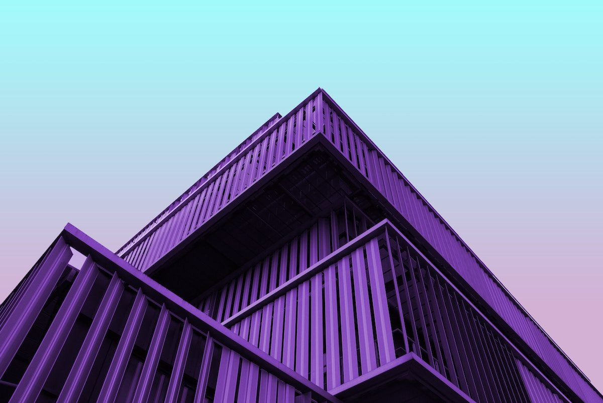 a purple building with a sunset in the background